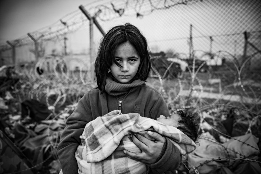 The refugee camp in Idomeni on the Greek-Macedonian border, to which thousands of immigrants, mainly Syrians, are coming. It is occupied by people from different social strata. They are all found there fleeing the war, death and starvation. They continue their journey through Macedonia to the north and west of Europe. Not everyone manages to pass the verification of the documents, which leads to the separation of families. The refugees are living in difficult conditions and sleeping in overcrowded and soaked tents. They are frozen and have limited access to sanitation. The refugees are exhausted, tired and uncertain about their situation.